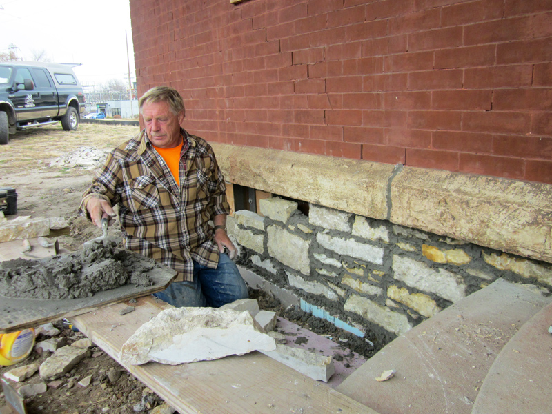 Ken Stenzel laying limestone facing on the foundation